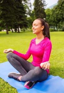smiling woman meditating sitting on mat outdoors