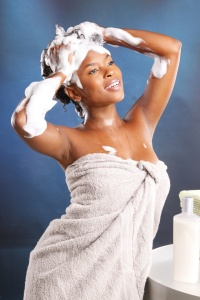 Cute African American using shampoo